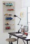 Shelves for toy cars on a wall with a desk and a retro lamp in front of them