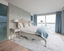 Doppelbett und Nachttisch vor Tapetenwand und Zugang zum Bad Ensuite in elegantem Schlafraum mit Seeblick