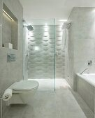 Toilet and bathtub in designer bathroom with marble tiles; walk-in shower with 3D structured tiles