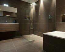 Hängewaschtisch neben begehbarer Dusche in puristischem Designerbad mit graubraunen, grossformatigen Fliesen