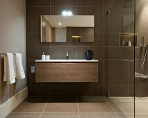 Hänge-Waschtisch neben der Glasabtrennung einer begehbaren Dusche in braun gefliestem Badezimmer