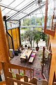 View from gallery down onto dining area in converted former greenhouse with brick floor