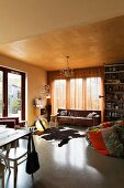 Patchwork beanbag and animal-skin rug in front of brown leather couch in cosy living area