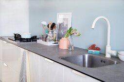 White kitchen counter with pale blue splashback, vase and kitchen utensils
