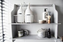 Masculine toiletries, shaving brush and decorative tin on vintage wooden shelves painted pale grey