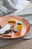 Mug of coffee, banana and toast on tray on bed