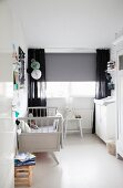 Retro cot, changing cabinet, grey roller blind and black curtains in nursery