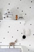 White wallpaper with pattern of black stars and two star-patterned cases on vintage bracket shelf