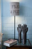Table lamp with lettering on lampshade and hand-shaped ornaments on small bedside table