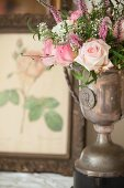 Bouquet of roses in antique silver trophy in front of botanical illustration