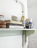 Books and cooking utensils on kitchen shelf