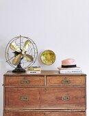 Old table-top fan on top of antique wooden chest of drawers
