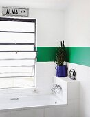 Bathtub below tilt window in white bathroom with green stripe along walls