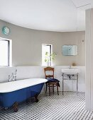 Blue-painted vintage bathtub, chair and washstand against curved wall in bathroom with black and white tiled floor
