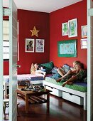 Children on bed in bedroom with pictures hung on red walls