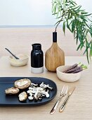 Various mushrooms on black dish, bowls and branch of leaves in wooden vase