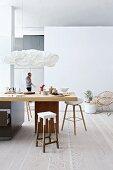 Bar stools around kitchen counter below designer pendant lamps in modern, open-plan interior with pale wooden floor