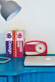 Retro radio, books and desk lamp on blue desk