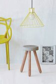 Stool with concrete seat and wooden legs below yellow pendant lamp