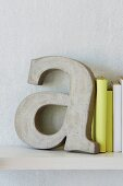 Decorative concrete letters used as bookends for books bound in white and yellow