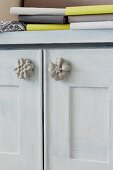 Concrete flower furniture knobs on doors of cabinet painted pale grey