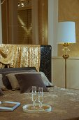 Elegant double bed with shimmering gold fabric draped over headboard next to standard lamp