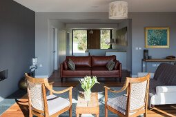 Cane chairs with seat cushions in sunlight and brown leather couch in modern open-plan interior with view into foyer