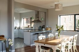 Traditional dining area with white-painted chairs in front of open-plan, pale designer kitchen with breakfast bar