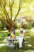 Family in sunny, summery garden around set table under shady tree