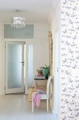 Open frosted glass door, Baroque chair and lace-patterned ceiling lamp in foyer