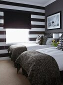 Twin beds, accent wall in wide black and white stripes and black fabric roller blind in small bedroom