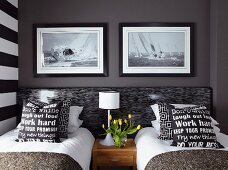 Black and white scatter cushions with lettering on covers on twin beds below photos of sailing boats on dark wall