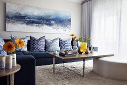 Seascape on wall above sofa with blue scatter cushions and simple wooden tables