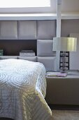 Glossy cover on bed against upholstered wall panels and table lamp on bedside table in bedroom in elegant shades of grey