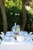 Table set with white tablecloth under shady trees in garden
