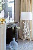 White allium flowers in floor vase next to modern standard lamp with white lampshade in corner