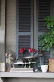 Vintage kitchen scales on masonry sill below grey window shutters