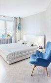 Blue retro armchair next to double bed with white headboard in modern bedroom