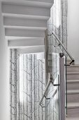 Stairwell with stainless steel handrail on glass balustrade and tree-patterned mural wallpaper in background