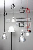 Pendant lamps at various heights with coloured cables and standard lamp against pale grey wall in background
