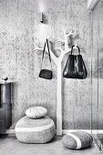 Floor cushions and bags hung on stylised tree as coat rack against wallpapered wall