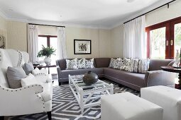 Large, elegant sofa combination in classic living room with pale and grey upholstered furnishings
