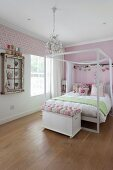 Double bed with white canopy frame and ottoman at foot on rustic wooden floor in pink-painted girl's bedroom