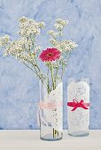 Doilies tied around simple, cylindrical vases with silk ribbons