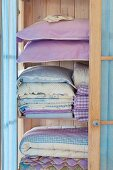 Stacks of pastel-blue bedclothes and pillows in a light wooden cupboard