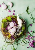 Pale violet macaroons in wicker nest with green ribon