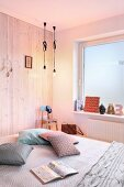 Wooden wall, window covered in frosted film and illuminated bulb-style pendant lamps in bedroom