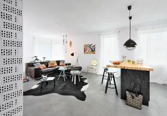Kitchen counter, side tables on cowhide rug and leather sofa in open-plan interior