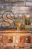 Candle lanterns and decorative wire letter on top of vintage chest of drawers against exposed brick wall