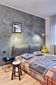 Concrete-grey bedroom with yellow accents and patchwork cover on double bed